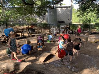 Young children playing in an outdoor sand and water area with a variety of loose parts.