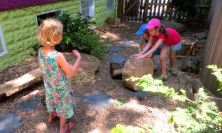 Children move a stump to another part of the yard.