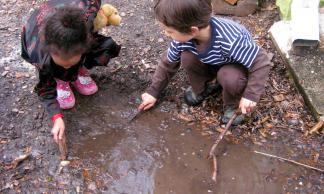 Children play in their mud aquarium.